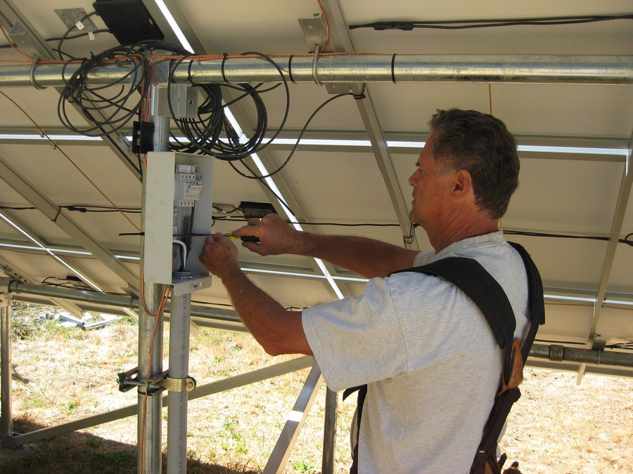 Photo of Rocky Thornton installing Solar Panels